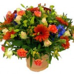 mixed flowers in a basket arrangement